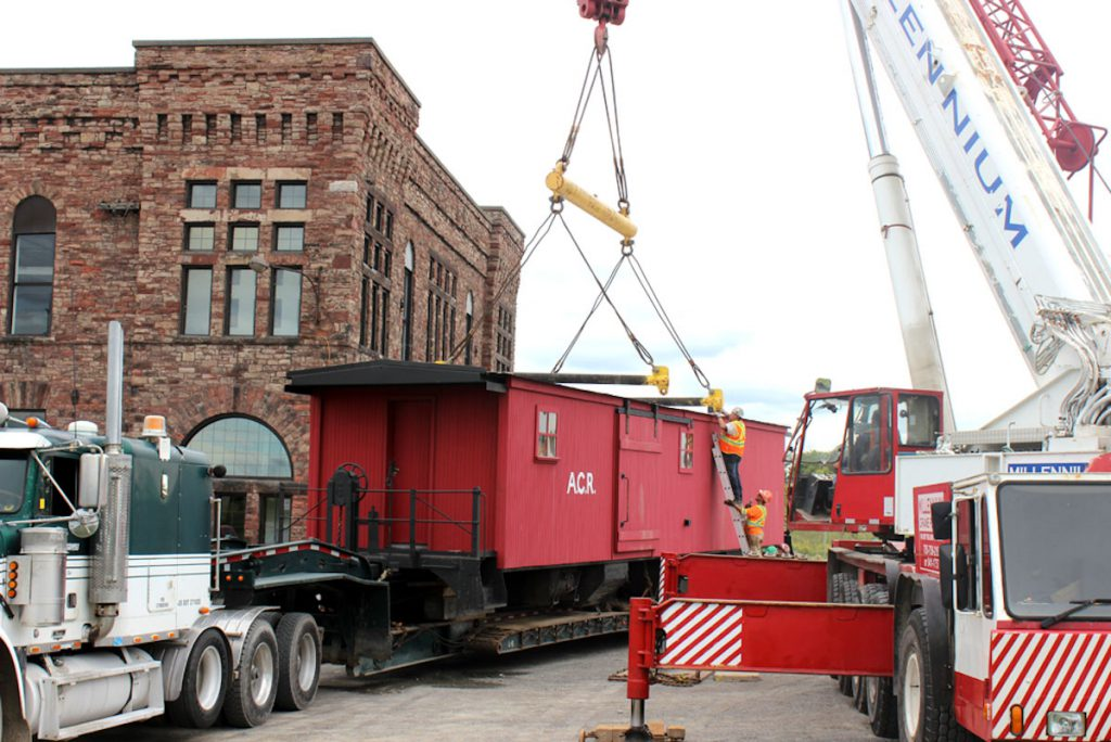 Lifting the boxcar off the float that brought the boxcar.