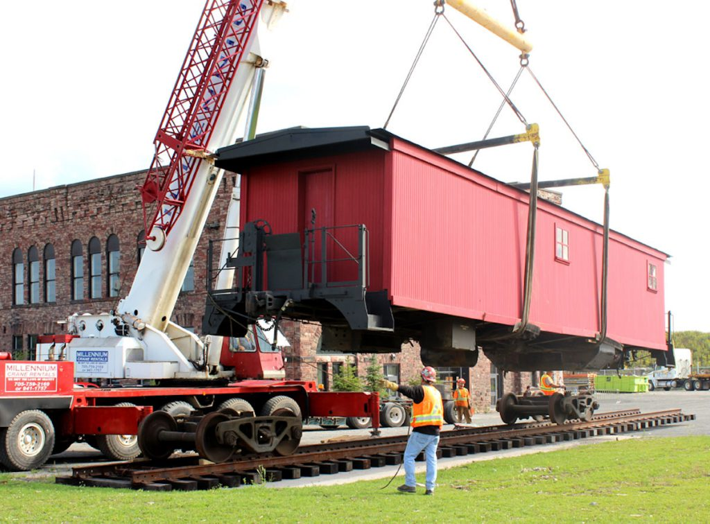 Preparing the boxcar to land on the wheels.