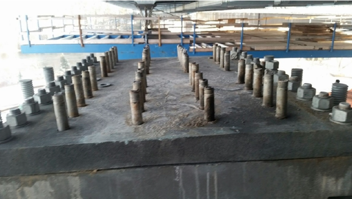 Figure 1-2: Fractured bolts (ASTM A490 bolt - connecting shoe plate to girder flange) and deformed shoe plate at north-west bearing. Note four lines of failed flange connection bolts. (Ministry of Transportation Nipigon River Bridge Independent Technical Review, by Associated Engineering, September 2016)
